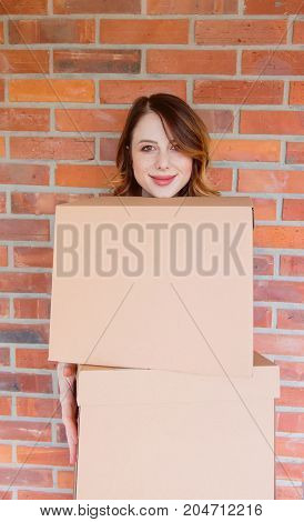 Woman In Jeans Shirt Standing On Brick Wall With Moving Box