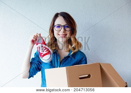 Woman In Jeans Shirt Standing On White Wall With Moving Box.