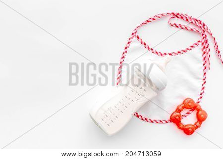 preparation of mixture baby feeding with infant formula powdered milk in bottle with bib on white desk background top view mockup