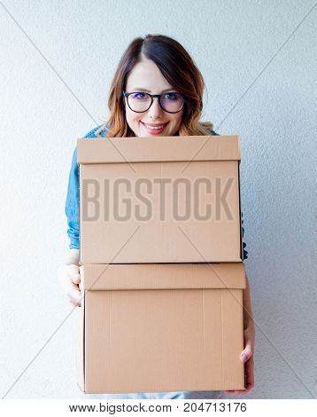 Woman In Jeans Shirt Standing On White Wall With Moving Boxes