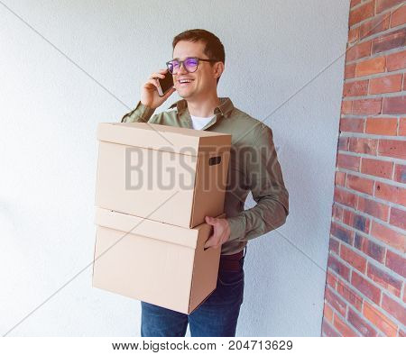 Handsome Man With Moving Boxes Calling By Phone
