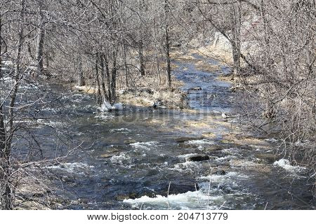 Winter landscape with a trough of melted ice and snow, cascading down a slight slope in early spring.