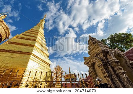 Wat Phra That Cho Hae Buddhism Temple with golden pagoda on blue sky background. Places worship of buddhists and attractions famous religion at Phrae Province Thailand