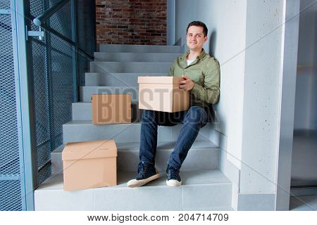 Handsome Man With Moving Boxes Sitting On Stairs