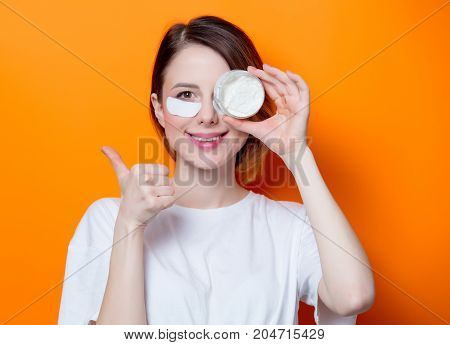 Woman Using Eye Patch For Her Eyes And Holding Cream