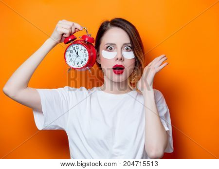 Woman Using Eye Patch For Her Eyes And Holding Alarm Clock