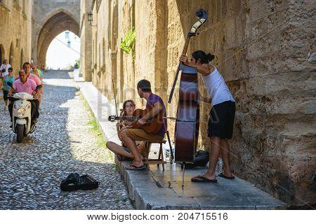 RHODES, GREECE - AUGUST 2017: Street musicians at narrow street of Rhodes town on Rhodes island, Greece
