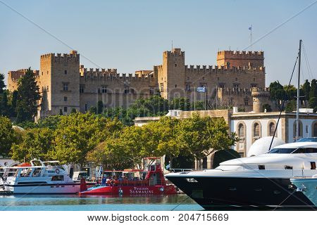 RHODES, GREECE - AUGUST 2017: Mandraki Harbor with medieval fortress on a background in Rhodes Town, Rhodes island, Greece