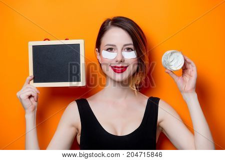 Woman Using Eye Patch For Her Eyes And Holding Blackboad And Cream
