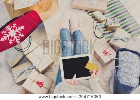 Christmas online shopping top view. Female buys presents to prepare to xmas eve at tablet with credit card, copy space on screen. Winter holidays sales.