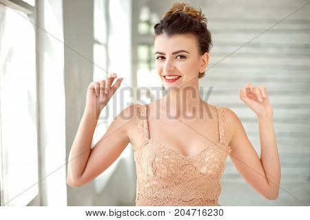 Half-length portrait of happy beautiful dark-haired woman wearing beige singlet spreading arms out at white room.