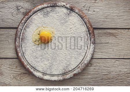 Baking concept. Sprinkled flour and egg yolk on wooden cutting board, cooking ingredients. Prepare for making yeast dough. Top view, copy space