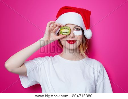 Woman Using Eye Patch For Her Eyes In Santa Claus Hat With Kiwi