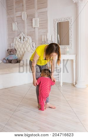 Cute little shy mixed race baby learning to walk, mom is holding his hands.