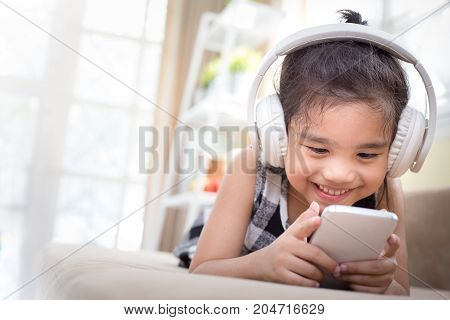 Happy Asian girl using headphone for listen music by smartphone while in the live room
