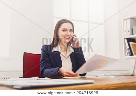 Business consulting. Young businesswoman talking by phone at modern office workplace