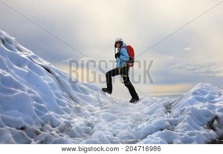 The girl dressed in a blue jacket and helmet on her head standing on the icy top of Falljokull Glacier (Falling Glacier) in Iceland