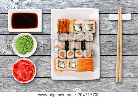 Japanese food restaurant delivery - sushi maki, unagi and roll platter set isolated on gray wood background, above view