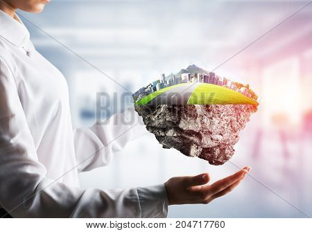 Closeup of business woman in shirt keeping green island with road and city in her hands with office view and sunlight on background. Mixed media.