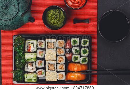 Colorful sushi and rolls platter in japanese restaurant, with teapot and chopsticks top view.