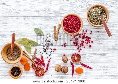 Variety of spices and dry herbs in ceramic bowls on light wooden kitchen table background top view mock-up