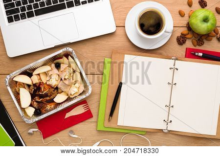 Healthy food delivery. Lunch box with diet meal on workplace, flat lay of wooden desktop with foiled container, copy space