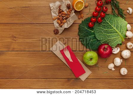 Border of fresh organic vegetables, fruits and nuts on rustic wood background. Healthy natural food on table with copy space. Cooking ingredients top view, mockup for recipe or menu