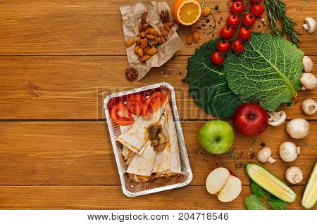 Healthy food delivery background. Lunch box with pancakes, chicken and tomatoes on rustic wood table, copy space