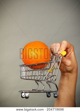 Buying healthy food vegetarian gluten free vegan products. Woman holding shopping cart with orange inside