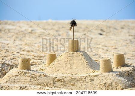 Sandcastle with wall and towers on the beach on a sunny day