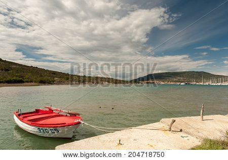 Small red boat in a bay in cres with a partly cloudy sky