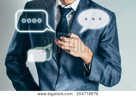 Businessman is holding mobile and chatting to people about internet of thing technology background.