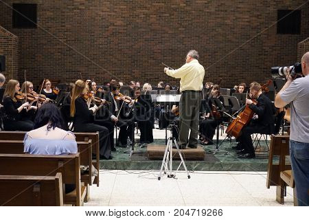 ROMEOVILLE, ILLINOIS / UNITED STATES - MAY 21, 2017: Dr. Lawrence Sisk conducts the Metropolitan Youth Symphony Orchestra (MYSO) in a dress rehearsal prior to a concert in Borromeo Hall at Lewis University.