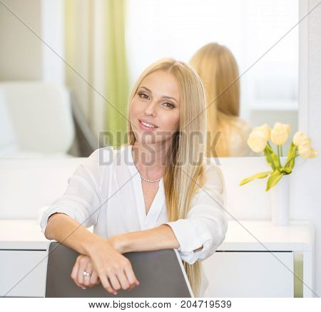 Portrait of young beautiful blonde hair woman sitting near dressing table at home.