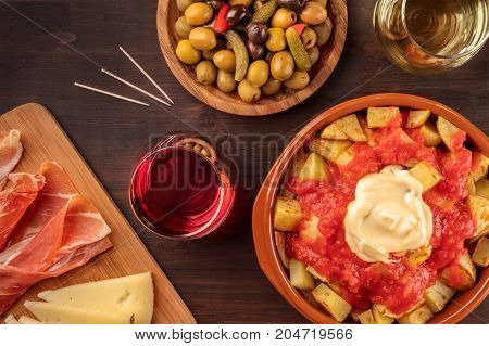 An overhead photo of traditional Spanish tapas. Pickled olives, patatas bravas, potatoes with a red and white sauce, jamon, and cheese, with glasses of wine, shot from above on a dark rustic texture