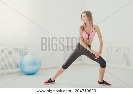 Fitness woman at stretching training at gym indoors. Young slim girl makes aerobics exercise. Healthy lifestyle, gymnastics concept