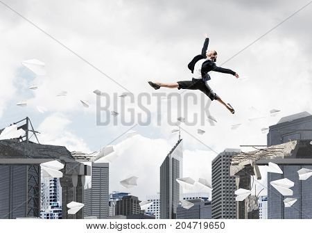 Business woman jumping over gap with flying paper planes in concrete bridge as symbol of overcoming challenges. Cityscape on background. 3D rendering.