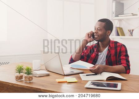 Business call. Young african-american businessman in casual has mobile phone talk in modern white office interior