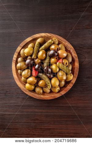 An overhead photo of a tapas mix of olives, mini gherkins, and other pickles, shot from above on a rustic texture with a place for text