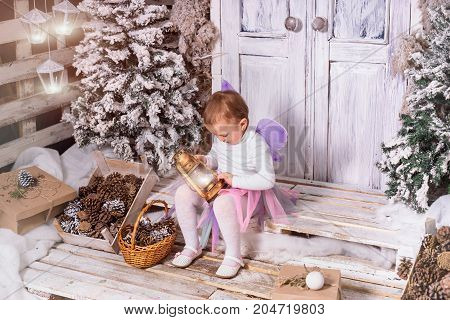 Horizontal shot of little girl wearing fairy costume and looking at latern in her hands.