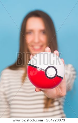 Ufa, Russia - July 8, 2017: woman holding pokeball. pokemon go multiplayer game with elements of augmented reality. Catching the Vaporeon pokemon
