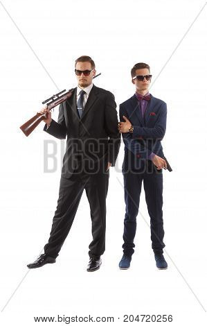 Two men in fancy suits and ties armed with guns.