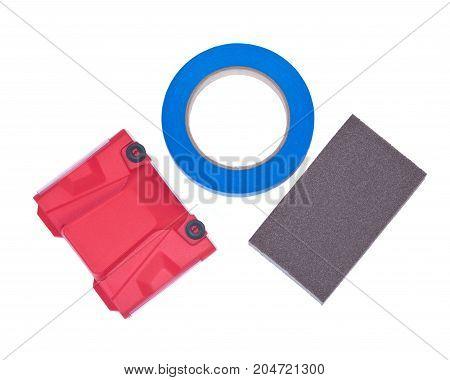 Blue painter's tape, jumbo sanding sponge and paint trimline edger isolated on white background