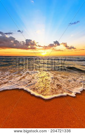Sunrise light shining on ocean waves. Golden sands