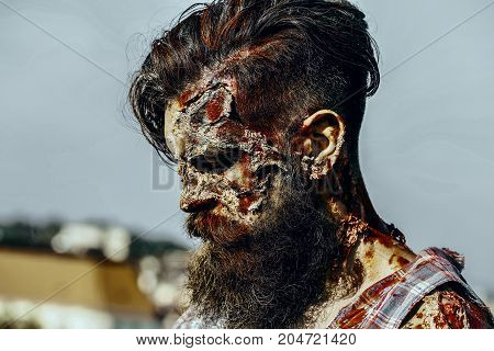 Halloween war soldier with wounds on face profile. Man with bloody beard and hair. Holiday celebration concept. Vampire hipster with red blood. Zombie on grey sky outdoors.