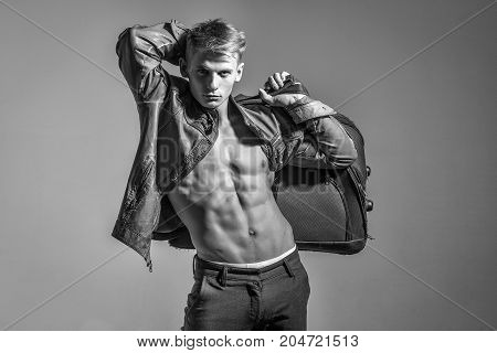 macho man with naked torso and sexy body holds big bag or suitcase in fashionable jacket and pants black and white
