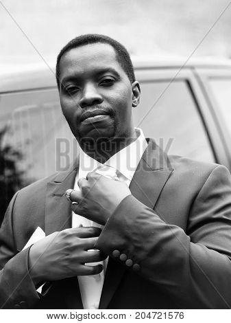 Handsome man african American groom in elegant suit coat for wedding ceremony fixes white tie outdoors
