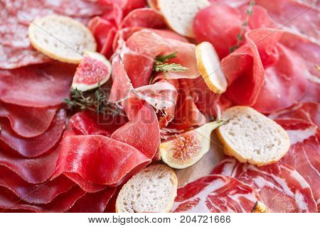 Italian antipasti and appetizers. board with slices prosciutto, salami, dried pork, salami ham with herbs. bread croutons
