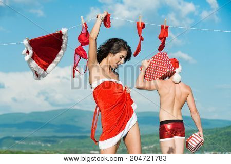 Couple in love of man and girl hanging clothes for drying. Christmas man and woman family. Laundry and dry cleaning. New year guy with muscular body on blue sky. Xmas red costume on rope with pin.