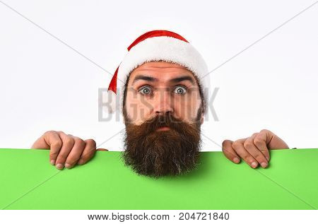 santa bearded man long beard brutal caucasian hipster with moustache on surprised face in christmas red hat for new year holiday with green paper sheet isolated on white background copy space